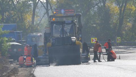 Modern heavy asphalt roller that stack and press hot asphalt. Yellow road repair Archivo