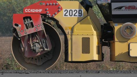 Modern heavy asphalt roller that stack and press hot asphalt. Yellow road repair Live Action