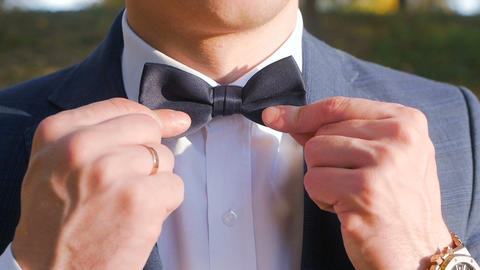 Man straightens bow-tie close up slow motion. Well-dressed young man puts and Footage
