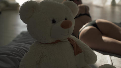 Young woman with perfect body in lingerie lying on the bed. Teddy bear on the Footage