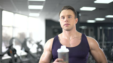 Muscular man drinking protein shake after workout, healthy diet, bodybuilding Live Action