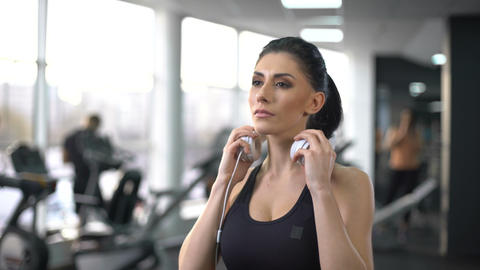 Active woman putting on headphones and enjoying music in gym, sport inspiration Live Action