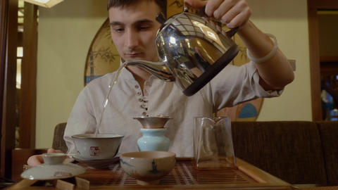 Tea master pouring hot water from kettle in gaiwan with tea on chinese ceremony Live Action
