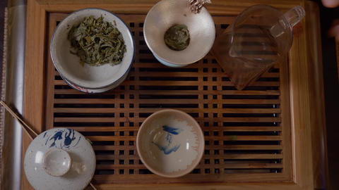 Master pouring hot water from teapot in gaiwan with green tea on tea table Live Action
