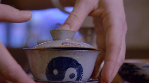 Closeup master pouring infusion tea from gaiwan in fairness bowl at tea ceremony Live Action