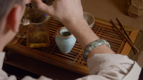 Master pouring green tea infusion from gaiwan in bowl. Chinese tea ceremony Live Action