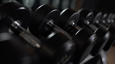 Closeup of male hand taking dumbbells, strength training equipment in gym Live Action