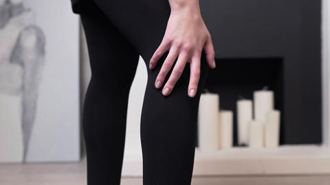 Woman runs her hand over her leg in black stockings, women's hosiery, women's Footage