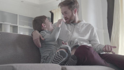 Bearded father and son are pampered and have fun together. Happy dad and child Live Action