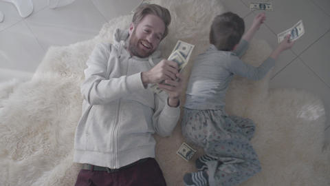 Parent and kid collect money scattered on the floor. Entertainment dad and child Live Action