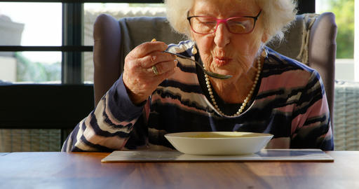 Senior woman having soup on dining table at home 4k Live Action