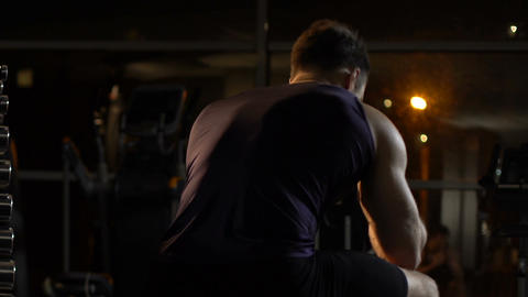 Depressed sportsman sitting in gym and thinking about problems, man in despair Live Action