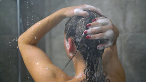 Woman washing her hair with shampoo. Hair care, beauty and wellbeing concept Footage