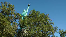 USA New York City 400 Statue of Liberty from behind between green foliage Footage