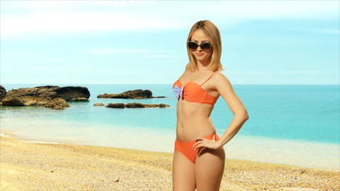 Girl blonde in swimsuit posing near the sea and enjoys dancing Footage