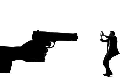 Silhouette of hand with gun threatening minuscule man, life in danger death risk Live Action