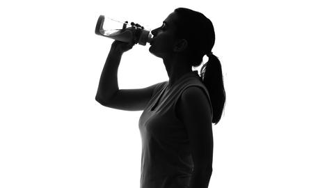 Sportswoman drinking beverage, keeping water balance after workout, healthcare Live Action