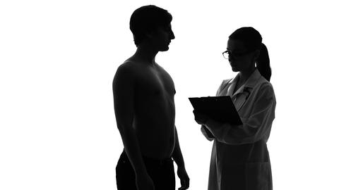 Silhouette of female doctor examining male patient, healthcare and medicine Live Action