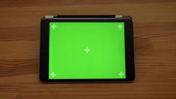 Approaching close-up horizontal view of tablet with green screen on wooden desk Footage