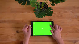 Top shot of woman s hands typing on green screen of horizontal tablet on wooden Footage