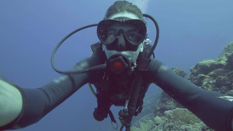 Portrait man scuba diver in mask and diver tank blowing air bubbles under sea Live Action