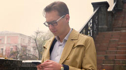 Closeup of attractive caucasian male typing on the phone calmly standing in the Footage
