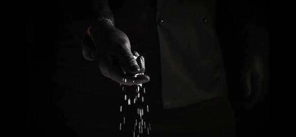 black latex gloved hand sprinkles white coarse salt on black background Archivo