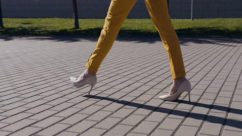 Female slim legs in high heels shoes walking in the urban street. Feet of young Footage