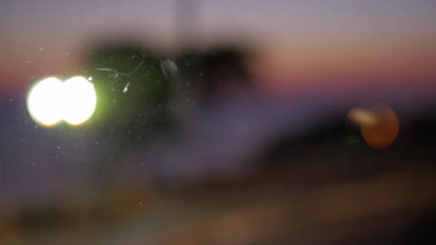 Blurred cars driving with headlights on. Evening view through the glass Footage
