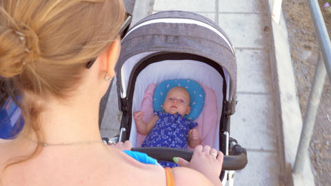 Mother pushing baby carriage in the street Footage
