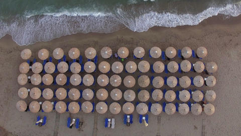 Sunbeds at the beach with few people relaxing there, aerial view Live Action