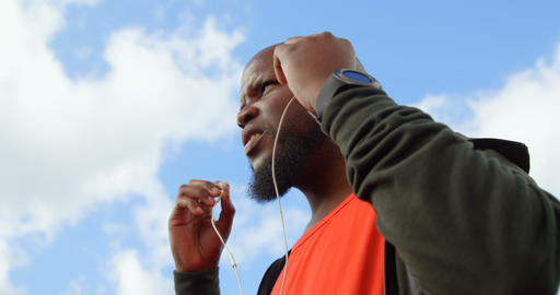 Low angle view of man listening music with earphone on a sunny day 4k Live Action