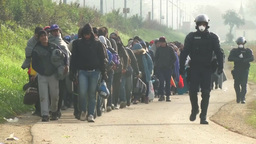 MIGRANT ESCORTED BY POLICEMEN WEARING RIOT GEAR AND MASKS EU Footage