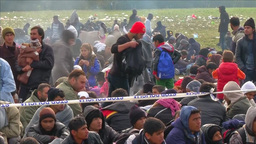 MIGRANTS SITTING IN FIELD BEHIND A TAPE BARRIER stock footage