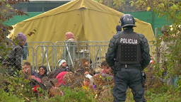POLICEMAN WITH REFUGEES AND BREZICE CAMP IN BACKGROUND EU MIGRANTS Footage