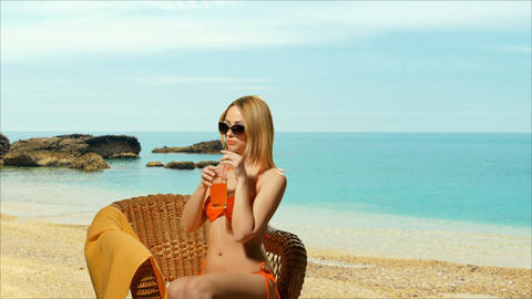 Girl blonde on the beach in swimsuit drinking juice Footage