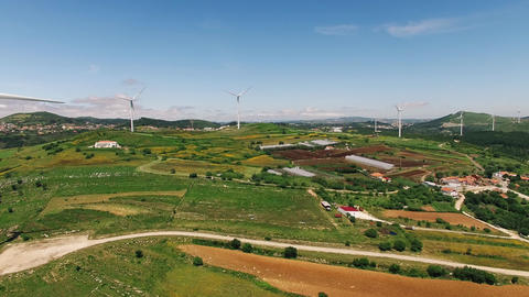 Wind power plants on a green hills aerial drone Live Action