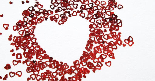Red hearts confetti forming a heart on white surface 4k Live Action