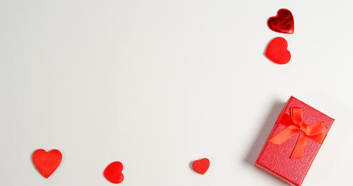Red gift box and red hearts on white surface 4k Live Action