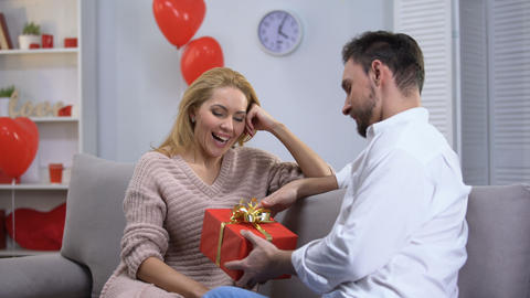 Boyfriend giving surprised happy lady gift for st Valentines day, happy couple Live Action