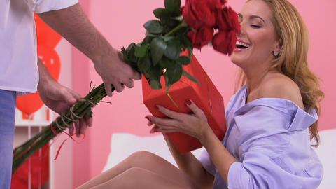 Man giving present and flowers to beloved woman on Valentines day, surprise Live Action