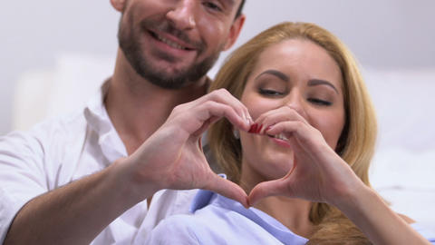 Couple making heart with hands, symbol of love and togetherness in relations Live Action