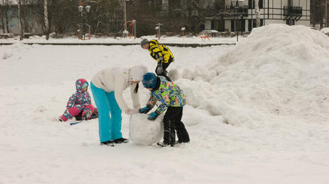 a mother with children, sculpts figures out of the snow フォト
