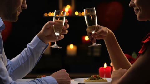 Handsome man tenderly holding female hand saying toast, candlelight dinner, fest Live Action