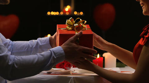 Courteous man presenting gift to his beloved woman, anniversary celebration Footage