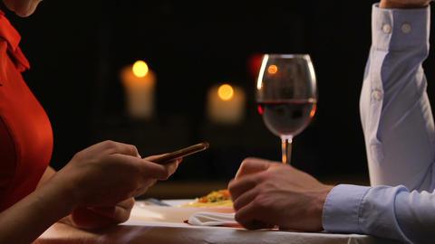 Girlfriend ignoring boyfriend, scrolling social network on smartphone, addiction Footage