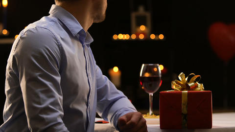 Frustrated boyfriend putting gift on table and leaving restaurant, break-up Footage