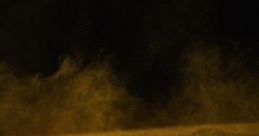 Golden glitter falling against black background 4k Live Action