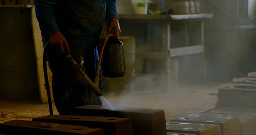 Male water spraying water on heated molds in workshop 4k Live Action