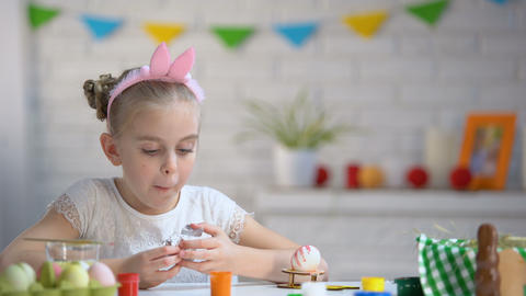 Small girl secretly eating chocolate egg, childhood, preparation for Easter Footage